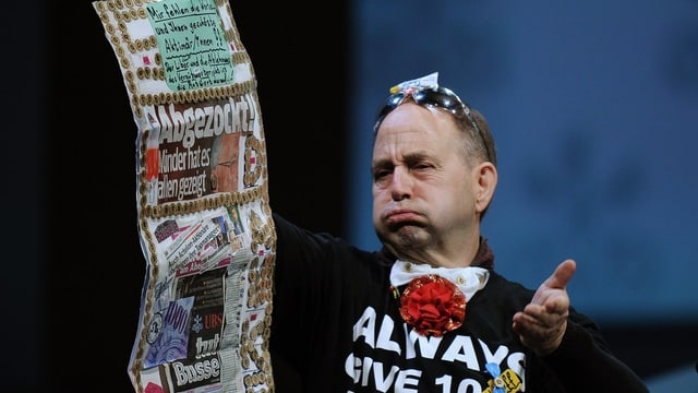Der Aktionär Peter Lampart auf der Bühne an der Generalversammlung der UBS. Er hält Zeitungsausschnitte in der Hand.