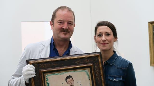 Ein Mann mit weissen handschuhen hält ein Gemälde.Rechts von ihm steht eine junge Frau.