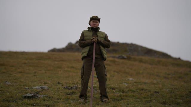 Putin in seinem Urlaub in der sibirischen Taiga auf einer grünen Ebene mit Stock.