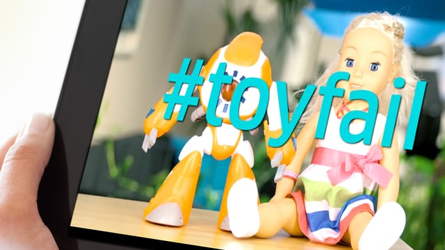 Ein Tablet, das zwei Spielzeuge – ein Roboter und eine Puppe – zeigt.
