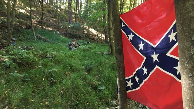 Ein Miliz-Soldat liegt im Wald, daneben hängt die Konföderierten-Flagge.