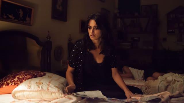 Eine dunkel gekleidete Frau sitzt auf einem Bett.
