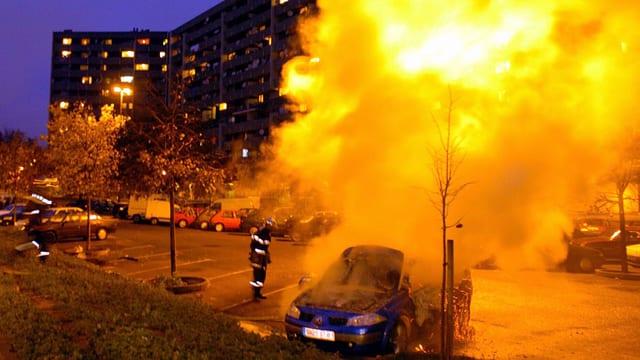 Ein brennendes Auto steht vor einem Wohnblock.