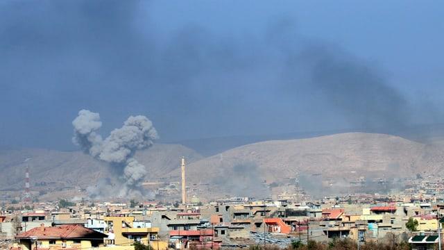 Explosionswolken über Häusern einer Ortschaft.