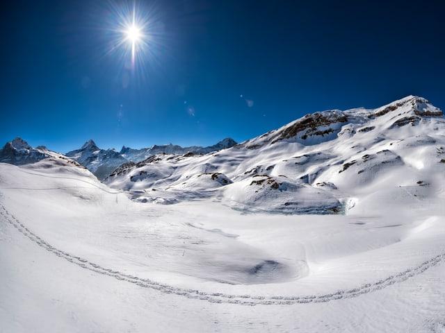 Wolkenloser Himmel über Schnee und Eislandschaft mit Spur im Schnee.