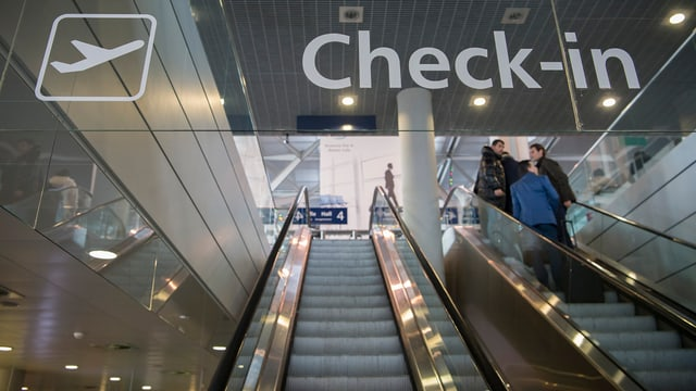 """Rolltreppen auf dem Euroairport, im Vordergrund die Schrift """"Ckeck-in""""."""