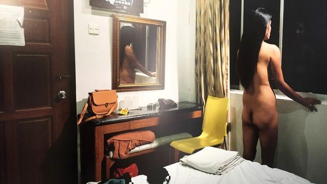 Nackte Frau von hinten in einem Zimmer.