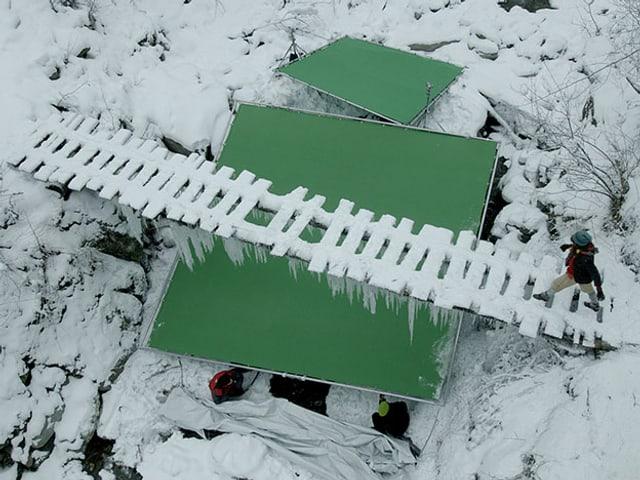 Verschneite Holzbrücke über der Schlucht mit einem Greenscreen.