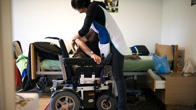 Eine Pflegerin hilft einem Behinderten in seinen Rollstuhl.