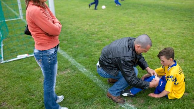Ein Mann bindet seinem Sohn, der im Fussballleibchen auf dem grünen Rasen sitzt, den Schuh.