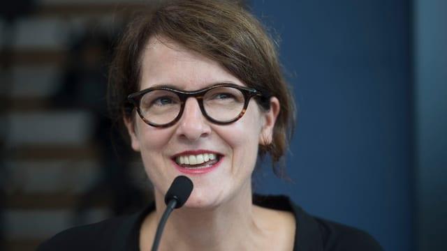 Frau mit lachendem gesicht hinter einem Mikrofon