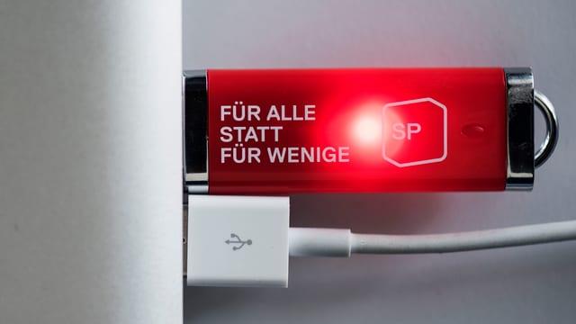 """Ein leuchtender USB-Stick mit dem SP Slogan """"Für alle statt für wenige"""""""