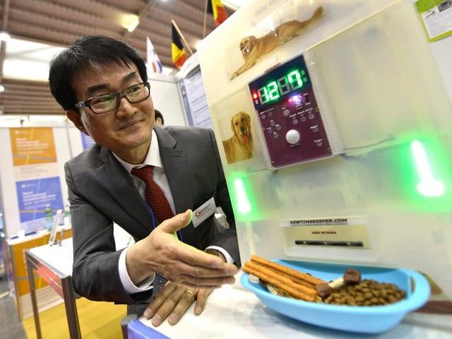Ein Südkoreaner präsentiert einen neuen Futterautomaten für Haustiere.