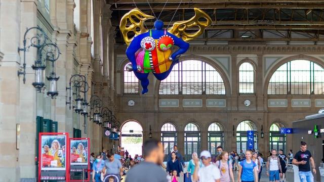 Ein bunter Engel in einer vollen Bahnhofshalle.