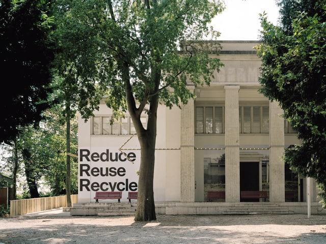 Der Deutsche Pavillon an der Biennale. Vor ihm ist ein Baum. An der Wand des Pavillons steht «Reduce, reuse, recycle»
