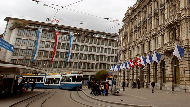 Paradeplatz in Zürich, Fassaden von UBS und CS und Tramhaltestelle davor.