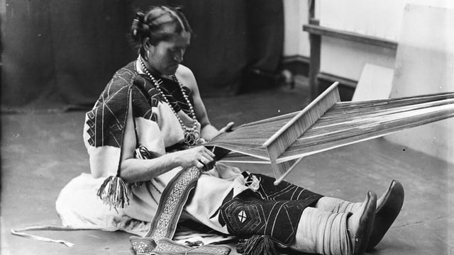 Schwarzweiss Foto eines indigenen Mannes, der Frauenkleidung trägt und webt.