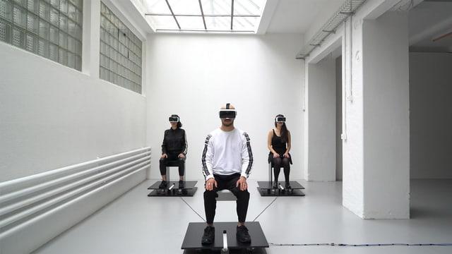 Drei Personen mit VR-Brillen sitzen in einem Raum.