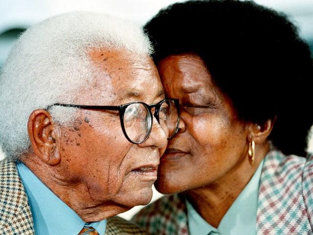 Zwei Menschen, eine Frau und ein Mann, halten ihre Köpfe eng beieinander.