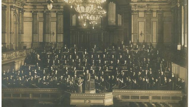Ein schwarz-weisses Foto zeigt ein Orchester in einem grossen Saal.