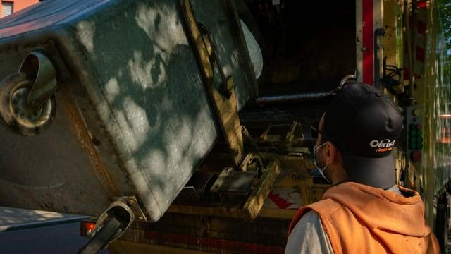 Ein Mann schaut wie der Abfall aus dem Container in die Kehrichtabfuhr verladen wird.