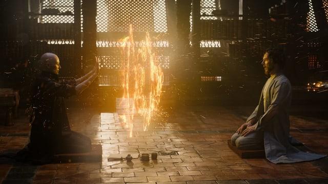 Filmszene aus Doctor Strange: Zwei Personen knien sich gegenüber in einem Schrein.