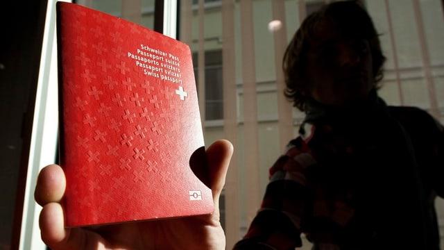 Eine unbekannte Person hält eine Schweizer Pass in die Kamera.
