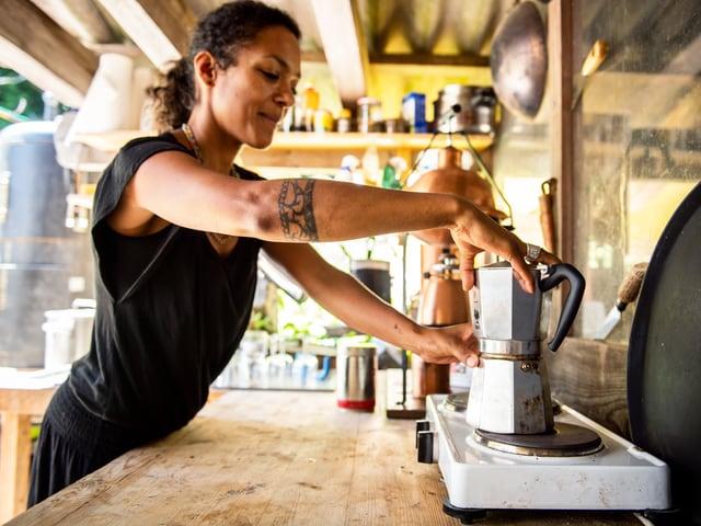Eine Frau steht vor einer 2er-Herdplatte. Darauf eine Bialetti-Kaffeemaschine.