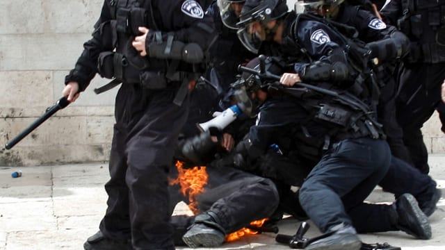 Polizisten, einer mit brennenden Kleidern.