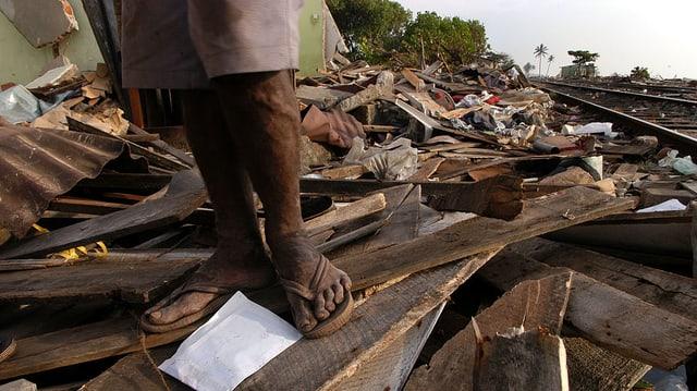 Schwarze Füsse stehen auf einem vom Tsunami verwüsteten Gebiet.