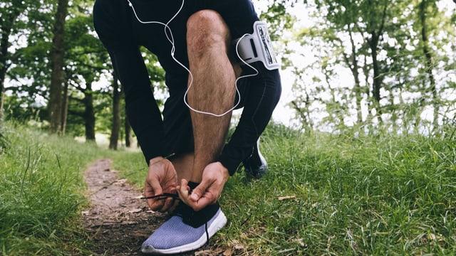 Ein Jogger mit Kopfhörer bindet sich die Schuhe.