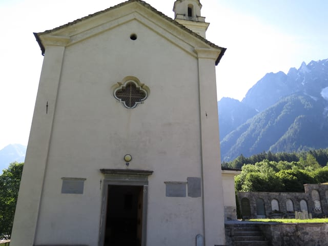 Ein kleine weisse Kirche mit grünen Bergen im Hintergrund.