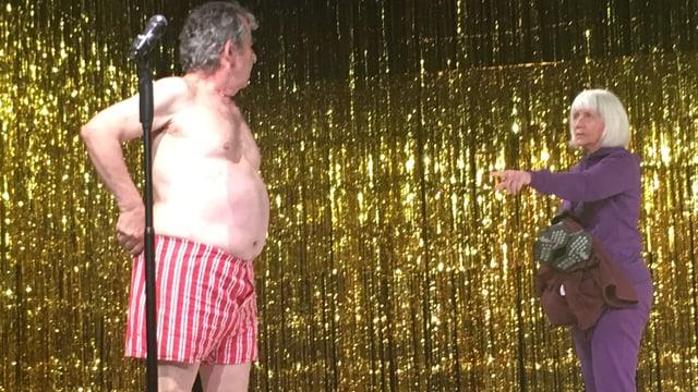 Ein älterer Mann steht nur in seiner Unterhose auf der Bühne und wird von einer Frau aufgefordert, die Unterhose nicht auch noch auszuziehen.
