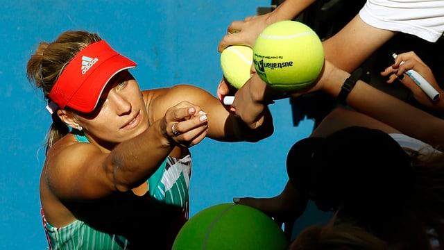 Angelique Kerber unterschreibt nach ihrem Halbfinalsieg auf Tennisbällen.