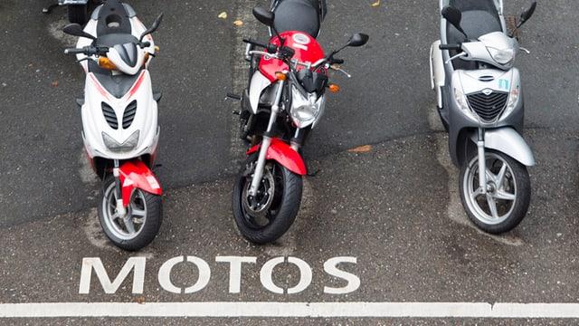 """Motorräder stehen auf einem Parkplatz, der extra für Motorräder ist. Man sieht die Aufschrtift """"Motos"""" am Boden."""