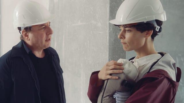 Ein Mann spricht mit einer Frau, die ein Baby in einer Tragtasche vor ihrem Körper trägt. Beide Erwachsenen tragen Bauarbeiterhelme.