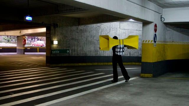 Van Eck geht durch ein Parkhaus, auf dem Rücken trägt sie zwei grosse, gelbe Lautsprecher, die aussehen wie Flügel.
