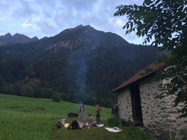 Eine Gruppe Menschen steht neben einer Hütte am Feuer. Jemand bläst in die Glut.