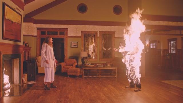 Eine Frau beobachtet schockiert eine brennende Person