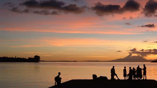 Umrisse von Menschen auf einem Hügel am Strand bei Sonnenuntergang.