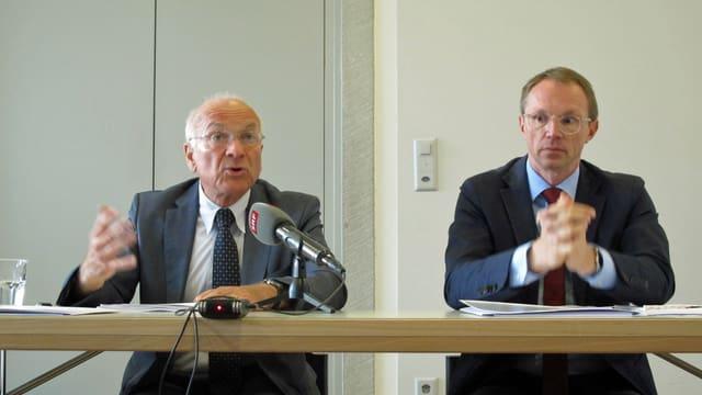 zwei Männer sitzen an einem Tisch, Mikrofon vor ihnen
