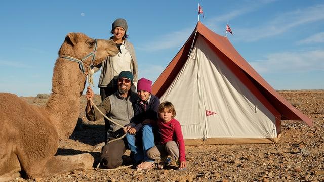Familie sitzt mit einem Kamel vor einem Zelt.