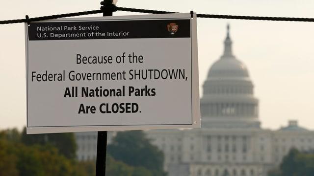 im Hintergrund das Kapitol in Washington, im Vordergrund ein Plakat, dass darauf hinweist, dass die Nationalparks wegen des Shutdowns geschlossen bleiben.