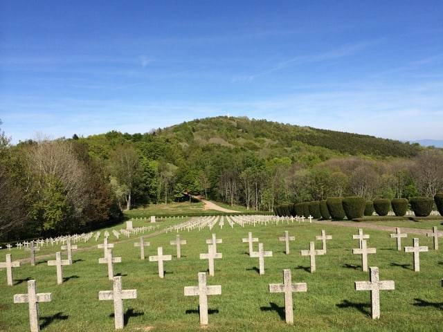 Vor einem bewaldeten Hügel stehen auf einer Wiese zahlreiche Gräber, die mit Kreuzen markiert sind.
