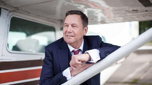 Der Sänger steht unter dem Flügel eines kleinen Motorflugzeugs.