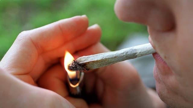 Ein Mann zündet einen Joint an.