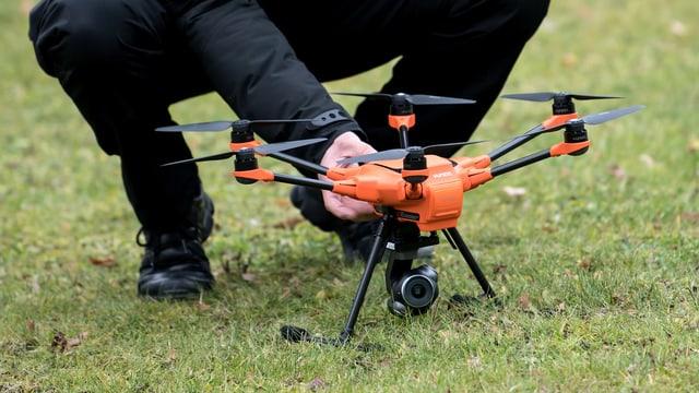Mann kniet vor einer Drohne.