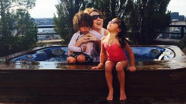 Mariah Carey mit ihren Zwillingen Moroccan und Monroe an einem kleinen Pool sitzend.