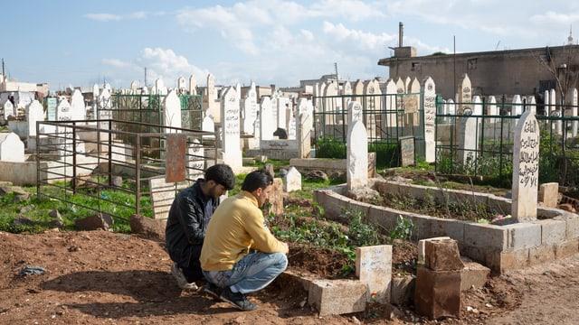 Zwei Männer trauern an einem Grab.