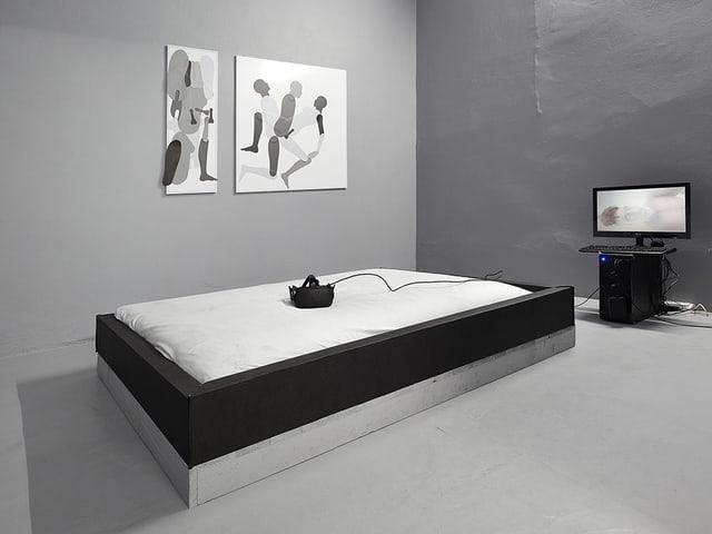 Ein Bett, darauf eine virtual Reality Brille, dahinter ein Bildschirm.